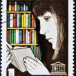 Royalty-Free Stock Photo: Stamp shows a young woman reading a book in a library