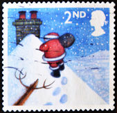 UNITED KINGDOM - CIRCA 2004: A stamp printed in England, shows Santa Claus, walking toward chimney in snow, circa 2004 — Stock Photo