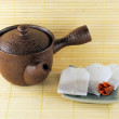 Royalty-Free Stock Photo: Teapot with tea bags on a little plate on bamboo background