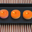 Stock Photo: Orange candles in black dish on bamboo