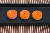 Orange candles in black dish on bamboo — Stock Photo