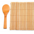 Wooden spoon beside bamboo placemat — Stock Photo