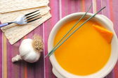 Pumpkin soup on purple cloth table with garlic — Stock Photo