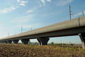 High speed train elevated railway in farmlands — Stock Photo