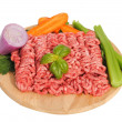 Raw ground beef with vegetables on wooden cutting board — Stock Photo
