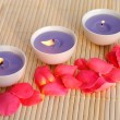 Three purple candles with rose petals on bamboo — Stock Photo