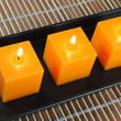 Stock Photo: Three orange candles in black dish on bamboo