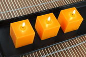 Three orange candles in black dish on bamboo — Stock Photo