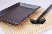 Sushi sticks and black plate — Stock Photo