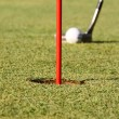 Royalty-Free Stock Photo: Club hitting a golf ball on the green