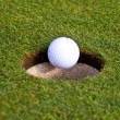 Golf ball is going in an hole — Stock Photo