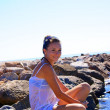 The girl sitting on a stone at the — Stock Photo #7251153