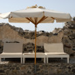 Deck chairs and parasol in Santorini, Greece — Stock Photo #6867652