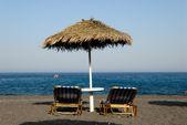 Liegestühle am strand von kamari auf santorini, griechenland — Stockfoto