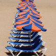 Stock Photo: Row of sun loungers on beach
