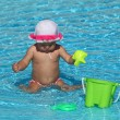 Cute toddler girl playing in the pool — Stock Photo
