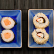 Sushi maki and california rolls on black bamboo mat — Stock Photo