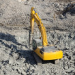 Yellow excavator at a construction site - Photo