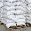 Stock Photo: Stacked white sacks at storehouse