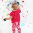Little toddler girl painting with colors on white wall — Stock Photo #7806668