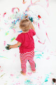 Little toddler girl painting with colors on white wall — Stock Photo