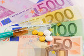 Syringe and pills on money background — Foto Stock