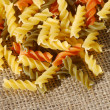 Colorful spiral shaped pasta on jute — Stock Photo
