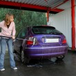 Young woman washing her car - Stock Photo