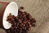 Coffee beans and paper cup — Stock Photo