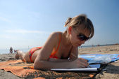 Girl lying on the beach and doing sudoku — Stock Photo