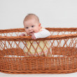 Little baby girl sitting in a basket — Stock Photo