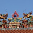 Dragons on the roof of taoist temple in Hong Kong - Stock Photo