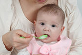 Mother feeds her little baby with spoon — Stock Photo