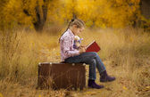 Little girl is reading a book in autumn — Stock Photo