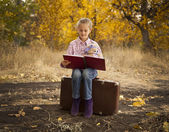 Little girl is reading a book in autumn wood — Stok fotoğraf
