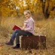 Little girl is reading book in autumn — Stock Photo #7279531