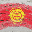 Flag of kyrghyzstan on grunge wooden texture painted with chalk — Stock Photo