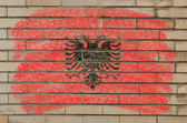Flag of albania on grunge brick wall painted with chalk — Stockfoto