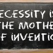 "Stock Photo: Proverb ""Necessity is mother of invention"" written on blac"