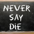 "Proverb ""Never say die"" written on a blackboard — Foto de Stock"