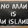 "Stock Photo: Proverb ""No mis island"" written on blackboard"