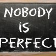"Foto Stock: Proverb ""Nobody is perfect"" written on blackboard"