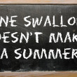 "Stock Photo: Proverb ""One swallow doesn't make summer"" written on bla"