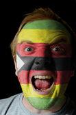 Cara de loco furioso pintadas en colores de la bandera de zimbabue — Foto de Stock