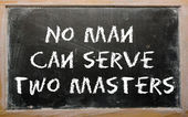 "Proverb ""No man can serve two masters"" written on a blackboard — 图库照片"
