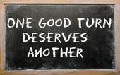 "Proverb ""One good turn deserves another"" written on a blackboard — Stock Photo"