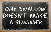 "Proverb ""One swallow doesn't make a summer"" written on a bla — Photo"