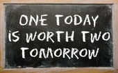 """Proverb """"One today is worth two tomorrow"""" written on a blackboar — Stock Photo"""