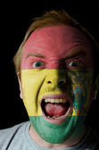 Face of crazy angry man painted in colors of Bolivia flag — Stockfoto