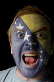 Face of crazy angry man painted in colors of Bosnia and Herzegov — Stock Photo
